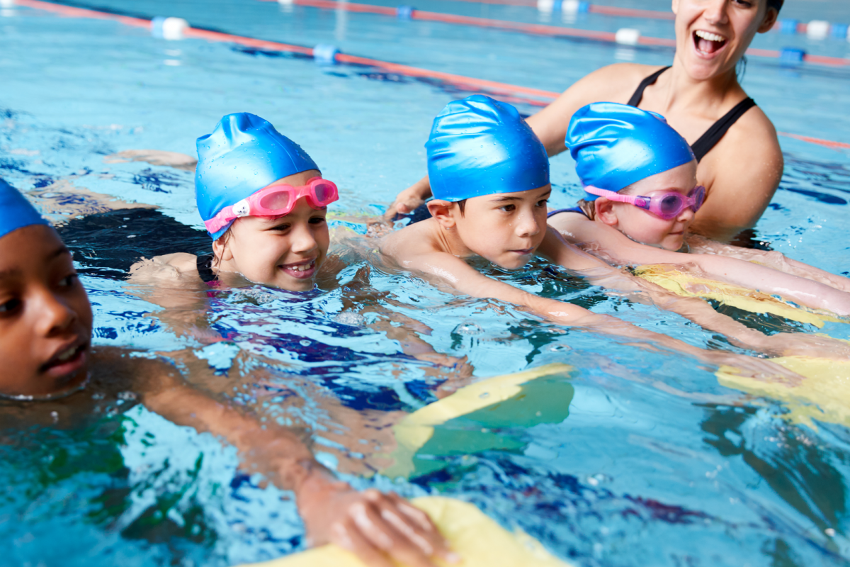 kids learn to swim with female instructor